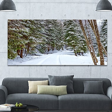 DesignArt 'Snowy Road in the Forest' Photographic Print on Wrapped Canvas; 28'' H x 60'' W x 1.5'' D