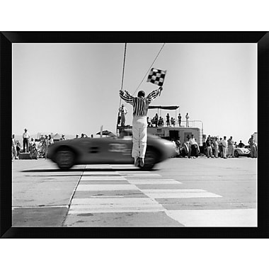 East Urban Home 'Man Jumping Waving Checkered Flag' Framed Photographic Print; 12'' H x 16'' W